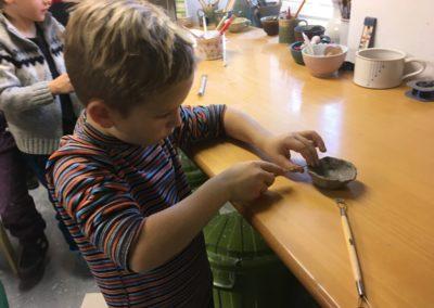 dítě při tvoření z keramiky